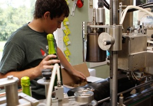 Incoming MU freshman Evan Strode prepares bottles for labeling.